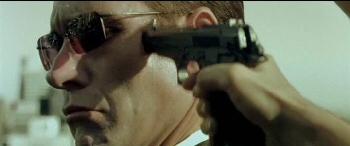 Trinity přikládá pistoli agentovi ke spánku...